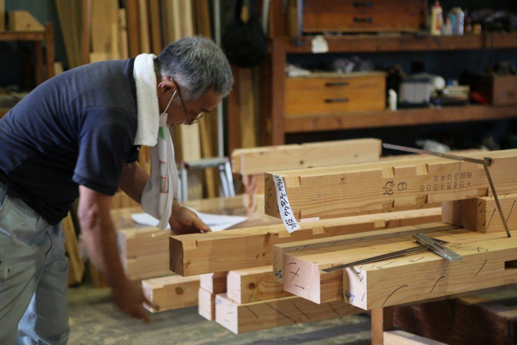 木材を眺める職人の画像